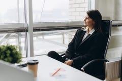Succesconceptie Portret van schitterende jonge businesslady zitting bij haar werkplaats in het bureau stock foto