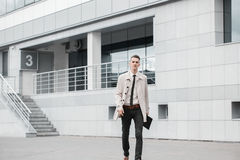 Succesful businessman walking down the street and smiling in day Stock Images
