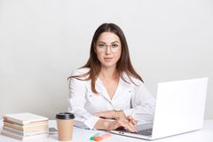 Succesful copywriter busy working with laptop computer, wears round glasses, drinks takeaway coffee, poses against white backgroun royalty free stock photography