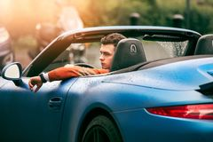 Succesful young adult handsome man drives luxury convirteble sport car at sunny day. Succesful young adult handsome man drives luxury convirteble sport car at royalty free stock photo