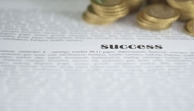 Success. The word success on the paper with another words and coins stock photography