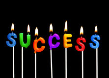 Success. Colorful rainbow candles spelling out success in a business celebration royalty free stock images