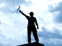 Success!!!. Man on a peak waving a flag depicting success Stock Photography