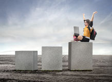 Success. Triumphing student sitting on the highest of three cubes with a laptop on her knees Stock Image