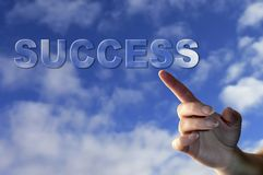 Success. Female hand with finger pointing at the word Success floating over a blue cloudy sky Stock Images