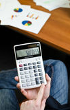 Success !. Calculator with success word on it display  holded by bussinessman in his office Royalty Free Stock Photo