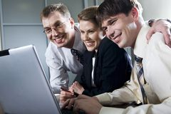 Success. Three smiling businessmen looking at the laptop Stock Photography
