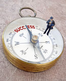 Success. Miniature businessman on a compass, with an arrow pointing to the word success Royalty Free Stock Image