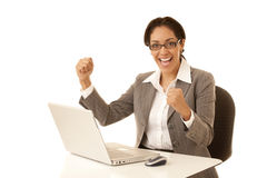 Success. Hispanic business woman sitting at desk with laptop computer clenching her fists in excitement isolated on white Royalty Free Stock Photography