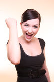 Success. Young professional looking woman fist pumping and looking happy in front of a peach background stock photos