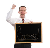 Success. A young businessman holding a sign and pumping his fist with excitement, isolated against a white background Royalty Free Stock Photos