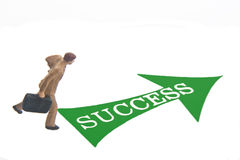 Success. Miniature business man with green arrow and SUCCESS text Royalty Free Stock Photo