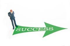 Success. Miniature business man with green arrow and SUCCESS text Royalty Free Stock Photos
