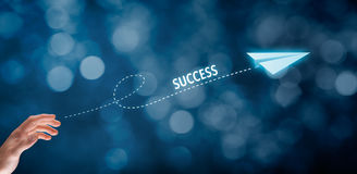 Success. Accelerate success concept. Businessman throw a paper plane symbolizing growing (accelerating) success. Wide banner composition with bokeh in background Stock Photography
