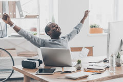Success achieved!. Beautiful young African man gesturing and smiling while sitting at the desk in creative office Stock Image