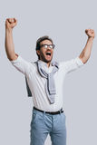 Success achieved!. Beautiful young man in smart casual clothes gesturing and shouting while standing against grey background Stock Photos