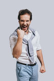 Success achieved!. Beautiful young man in smart casual clothes gesturing and shouting while standing against grey background Stock Image