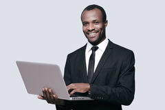 Success achieved!. Handsome young African man in formalwear working on laptop while standing against grey background Stock Photo