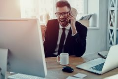 Success achieved. Handsome young man in formalwear talking on the phone and smiling while sitting in the office royalty free stock images