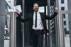Success achieved!. Handsome young man in full suit gesturing and smiling while standing outdoors stock images