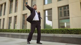 Success and achievement - happy businessman cheering celebrating looking at cell phone. Young urban professional. Successful business man receiving good news in stock footage