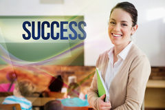 Success against pretty teacher smiling at camera at back of classroom. The word success against pretty teacher smiling at camera at back of classroom Royalty Free Stock Image