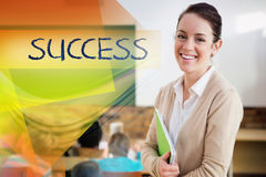 Success against pretty teacher smiling at camera at back of classroom. The word success against pretty teacher smiling at camera at back of classroom Royalty Free Stock Images