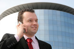 Success in business. Young businessman smiling and talking on a cell phone in front of a corporate building Royalty Free Stock Photography