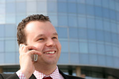 Success in business. Young businessman smiling and talking on a cell phone in front of a corporate building Stock Images