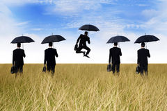 Success in Business. Business success: businessman jumping in front of his team Stock Photography