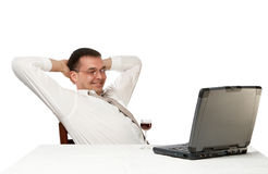Success business. Businessman having cast away on an armchair with a smile looks at the screen of a portable computer Stock Photo