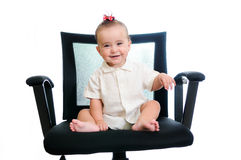 Success business baby in office armchair. A smiling baby girl with red ribbon sitting in an office chair, wearing a white shirt Stock Photography