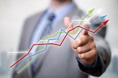 Success in business. Businessman pointing to growth on a line graph showing business success Stock Photo