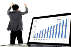 Success business man and growth graph. Focus on laptop monitor showing growth chart of sales and profit, out focus headache man in suit look sucess and happy Stock Photo