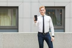 Success business man showing new smart phone and looking at camera. Stock Images