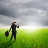Success Business woman holding bag in green rice field and raincloud Stock Image
