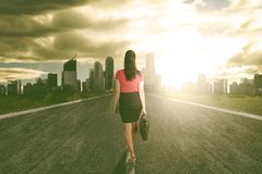 Success business woman walk towards the light heading to the city.  Stock Photo