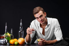 A confident young man drinking a whiskey or tequila in a club on a black background. A success businessman resting a pub Stock Photo