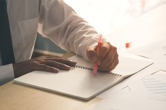Success businessman hand holding pink marker pen on hand and writing idea or somethings on notebook with business paper on wooden royalty free stock image