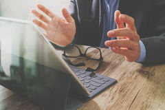 Success businessman hand using eyeglass,digital tablet docking s Stock Photography