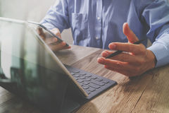 Success businessman hand using stylus pen,digital tablet docking. Smart keyboard on wooden desk Stock Photography