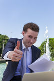 Success. Businessman with laptop and papers, thums up Stock Photo
