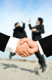 Success businessmen shaking hands. Two businessmen shaking hands with other two businessmen celebrating in the background, can be used for success concept Royalty Free Stock Photos