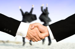 Success businessmen shaking hands. Two businessmen shaking hands with other two businessmen celebrating in the background, can be used for success concept Stock Photo