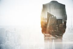 Success and career concept. Businessman standing on abstract city background with copy space. Double exposure Stock Images
