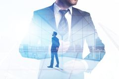 Success and career concept. Businessman standing on abstract office city background with sunlight. Double exposure Stock Image