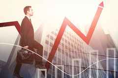 Success and career development concept. Man climbing stairs on abstract city background with upward red chart arrow. Success and career development concept Royalty Free Stock Image