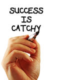 Success is catchy. Closeup of a hand writing a success is catchy message with a marker, possibly for a business strategy, isolated on a white background Stock Photo