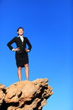 Success and challenges - business concept. Image. Successful business woman reaching goals overcoming challenges and adversity standing on mountain top in suit royalty free stock photo
