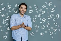 Emotional blogger laughing while reading the messages from his followers. Success. Cheerful young successful blogger feeling happy and laughing while reading Stock Image